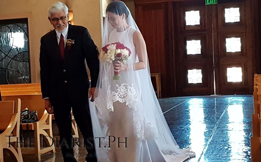 The father of the bride walks his daughter down the aisle at St. Vincent de Paul Church in Huntington Beach in California.